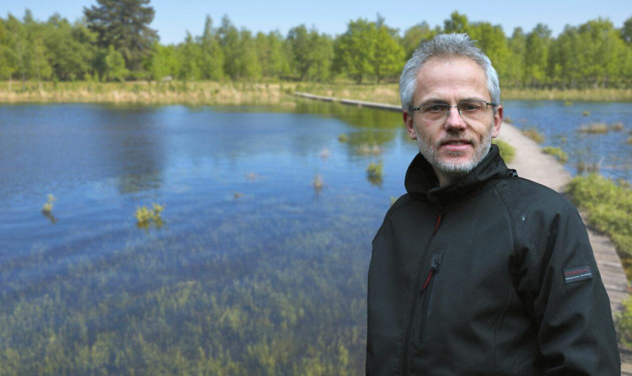 Portret van Adrie Otte voor water met bomen op de achtergrond