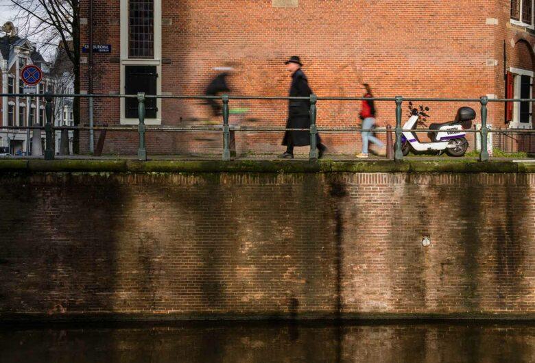 Wandelende mensen langs kade Amsterdam