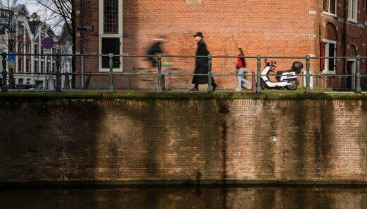 Wandelende mensen langs grachten Amsterdam