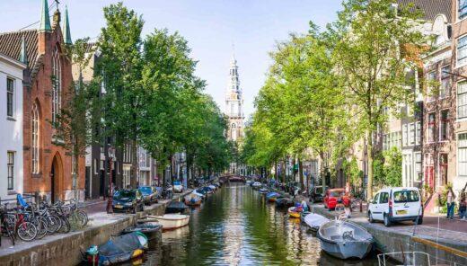 Gracht in Amsterdam met aan beide kanten grachtenpanden en uitzicht op de Westerkerk