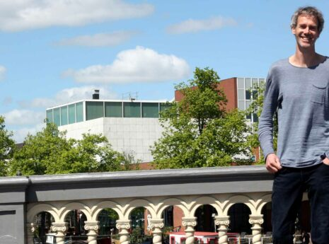 Architect Bas Horsting in Amsterdam leunend tegen een brug