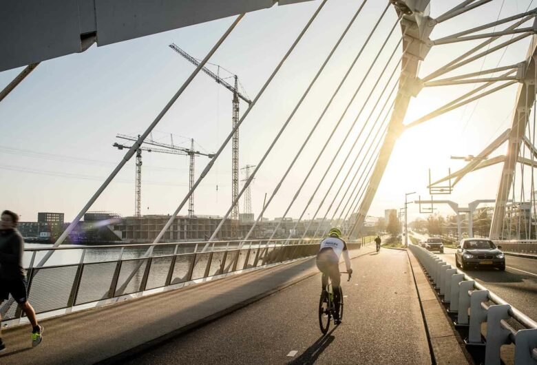 Hardloper en wielrenner op brug Amsterdam IJburg