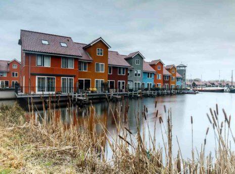 Gekleurde houten huizen in duurzame woonwijk aan het water