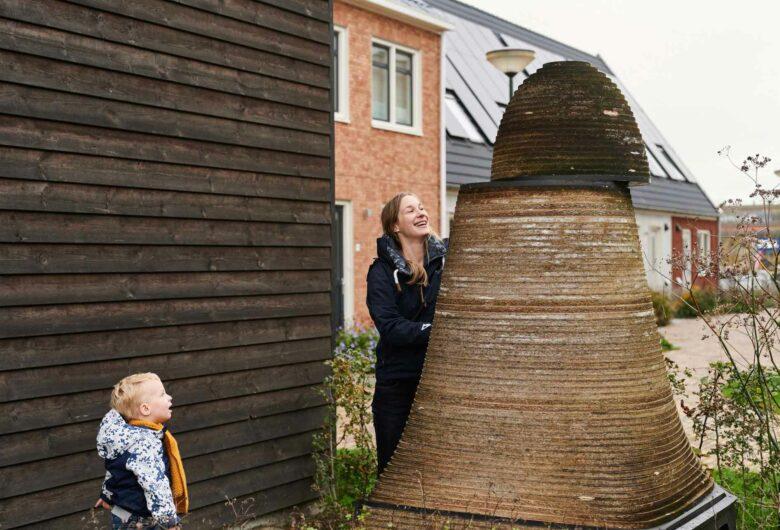 Vrouw en kind bij ecologische composthoop in woonwijk