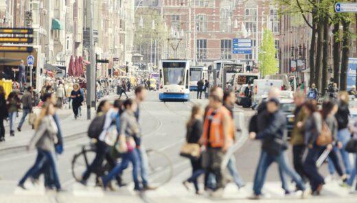 Overstekende mensen op het Damrak in Amsterdam