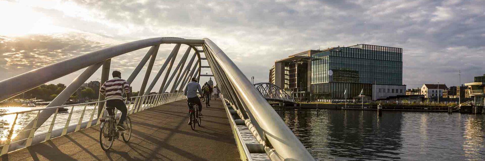 Fietsers op brug over water met gebouwen op de achtergrond