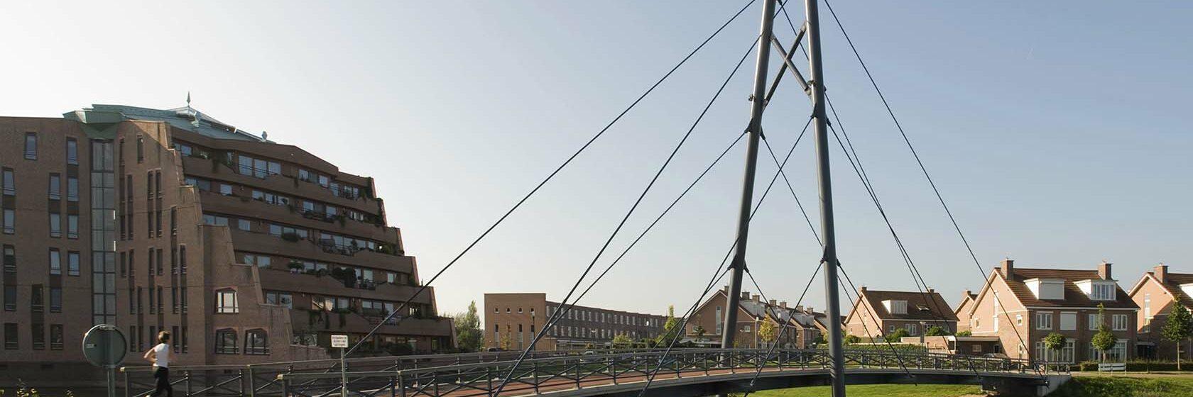 Brug over water met groen en gebouwen er omheen in Houten, Utrecht