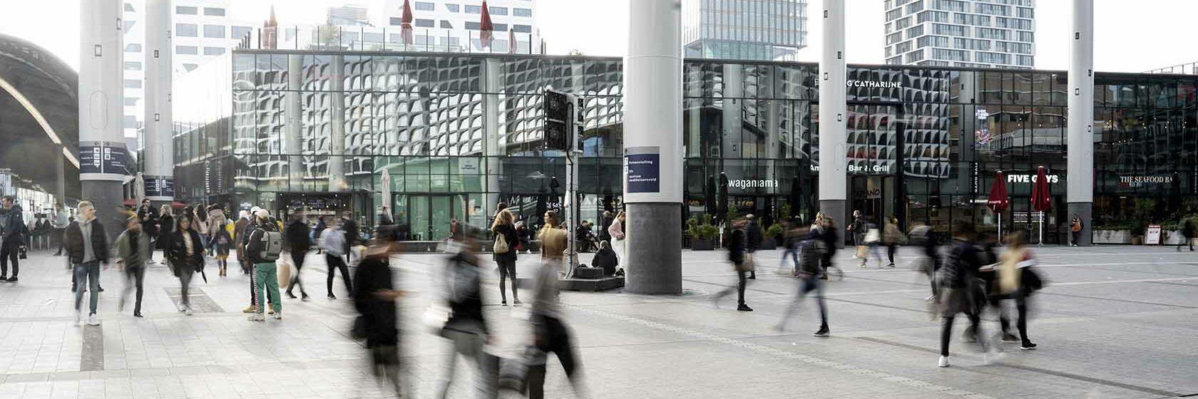 Mensen die wandelen op Hoog Catharijne Utrecht onder bollendak bij Utrecht Centraal Station