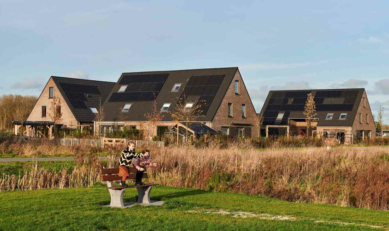 spelende kinderen in duurzame woonwijk met zonnepanelen op de huizen in Leeuwarden
