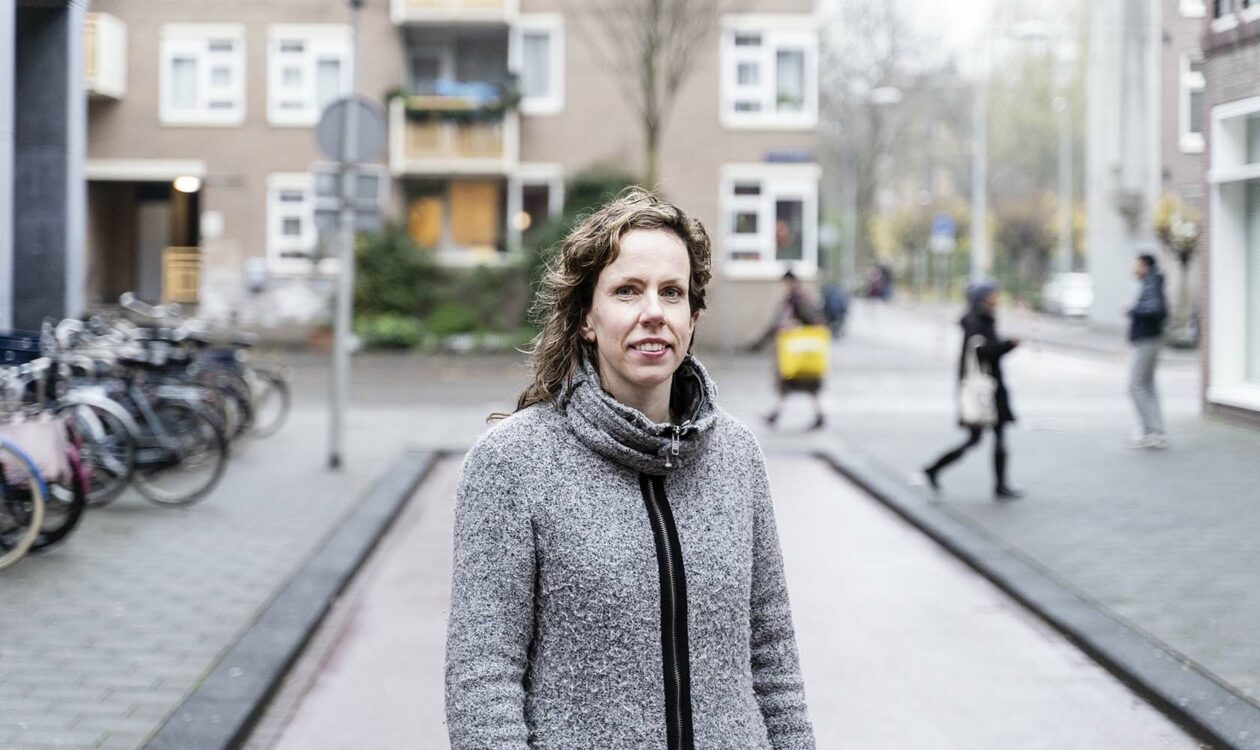 medewerker van Sweco op een straat met geparkeerde fietsen en met een aantal wandelaars op de achtergrond