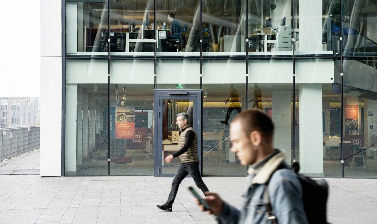 Moderne kantoorruimte en lopende mensen kijkend naar telefoon