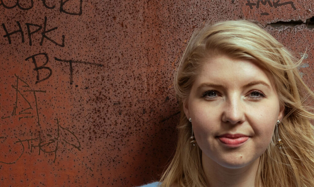 Portretfoto van Femke Tiegelaar medewerker van Sweco met een metalen roestige wand erachter