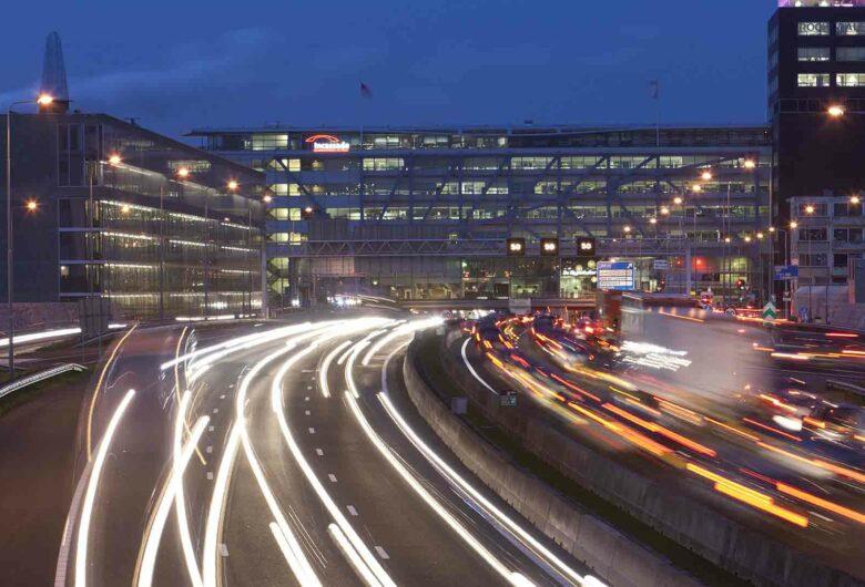 Infrastructuur in de nacht met wegen, gebouwen en auto's