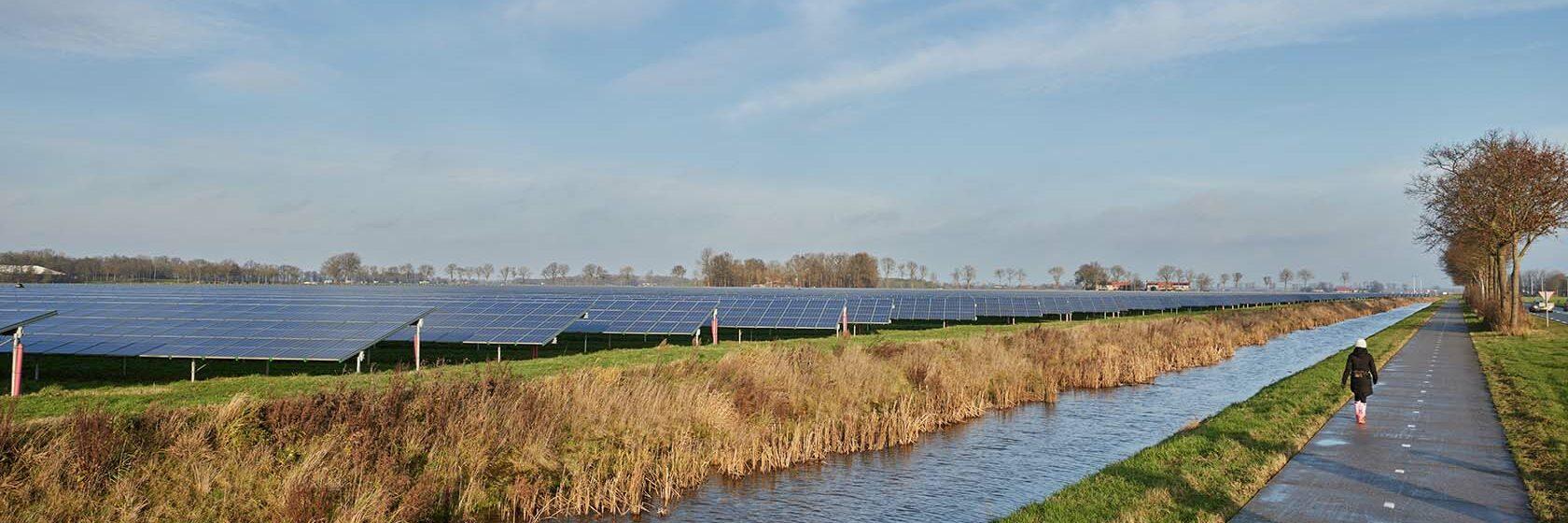 Fietser op weg naast zonnepark voor duurzame energie