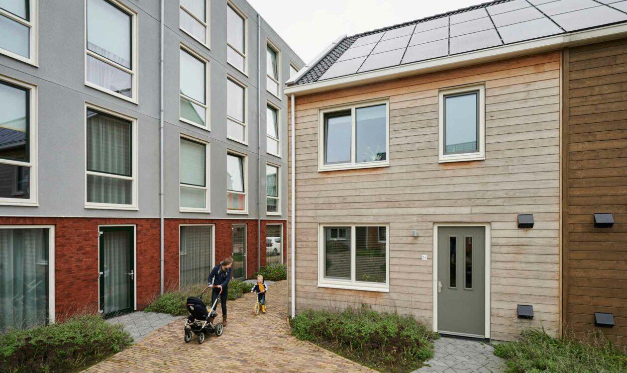 Ouder met kind op fiets en baby in kinderwagen naast een hoten huis met zonnepanelen