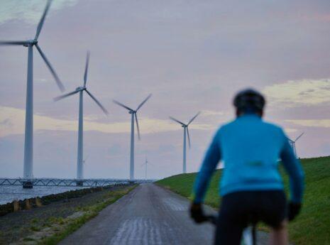Fietser in de schemering op een Ijsselmeerdijk met windmolens