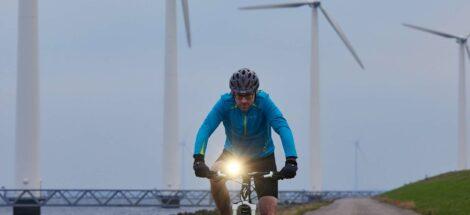 Fietser in de schemering op Ijsselmeerdijk met windmolens