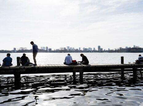 Mensen die op een steiger bij water zitten met skyline van Rotterdam op de achtergrond